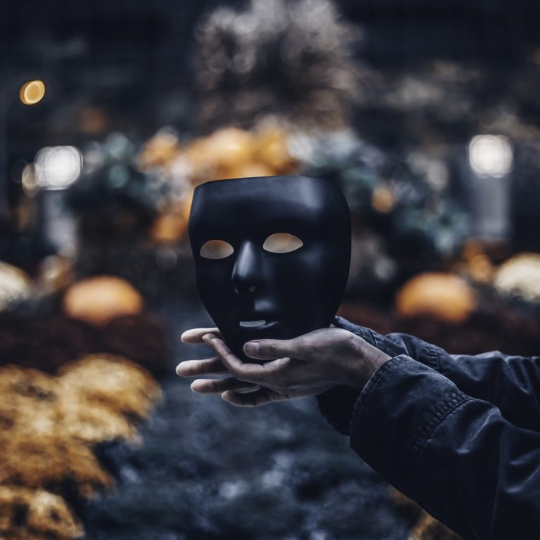Featured Image for Dealing with Impostor Syndrome: Here is what you need to know - Photograph of a man holding a mask