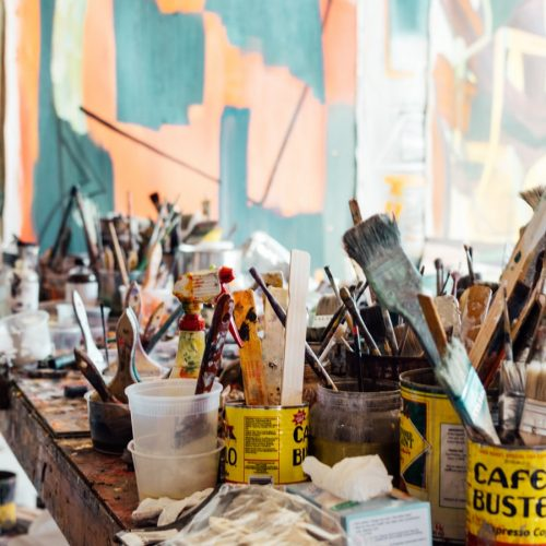 Featured Image for What is Cretivity? Evolution of Theories in Psychology - Painting Brushes and utensils on a table inside an art studio