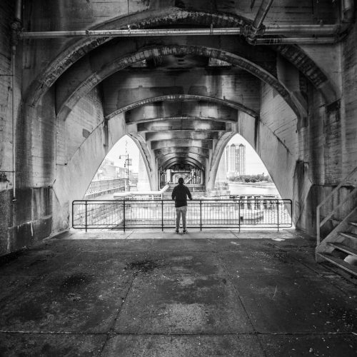 Feature Image for Theories of Emotions in Psychology: Quick Guide - Black and White photograph depicting a man contemplating under a bridge